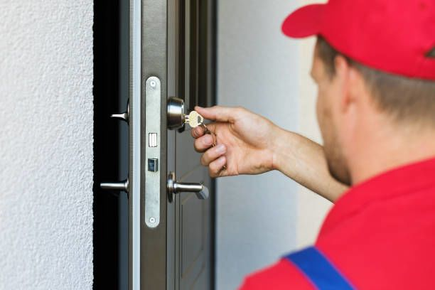door lock service – locksmith working in red uniform